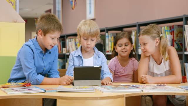 vídeos de stock, filmes e b-roll de ds crianças usando tablet na biblioteca - sem manga