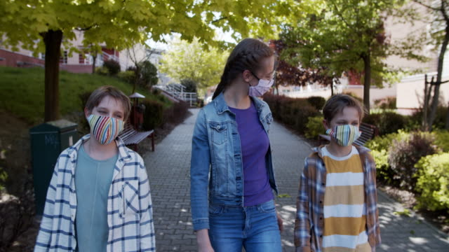 kids walking in residential district during covid-19 pandemic - dolly shot stock videos & royalty-free footage