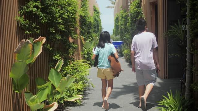 vídeos y material grabado en eventos de stock de niños caminando en día soleado en el camino a la habitación del hotel, concepto de vacaciones de verano. - alojamiento y desayuno