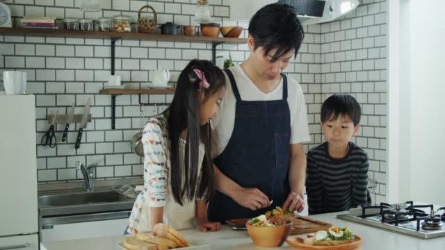 お父さんがモダンキッチンで昼食を作るのを見ている子供たち - preparing food点の映像素材/bロール