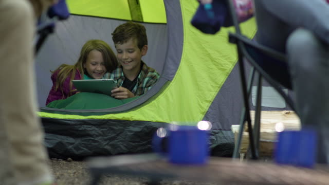kids watching tablet in tent