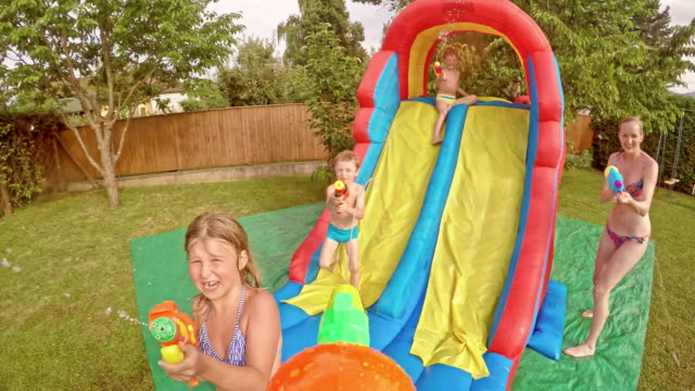 pov kids' water gun fight at a party - water slide stock videos & royalty-free footage