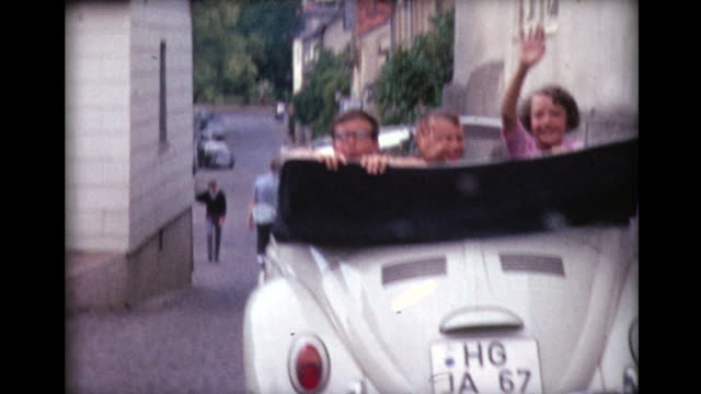 vídeos de stock, filmes e b-roll de 1967 kids wave from convertible volkswagen - home movie