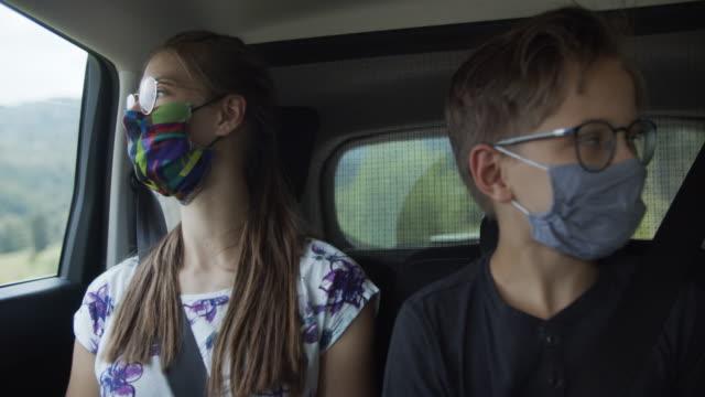 kids wearing anti virus marks travelling by car - passenger stock videos & royalty-free footage