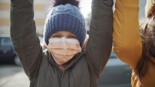 kinder, die antiviren-masken tragen, spielen draußen - mundschutz stock-videos und b-roll-filmmaterial