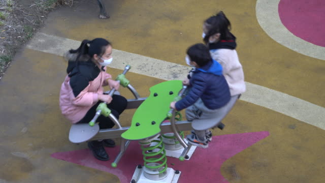 vídeos y material grabado en eventos de stock de kids wearing face mask are playing on a playground. because of the closure of schools and kindergarten, most of chinese kids have been required to... - neumonía