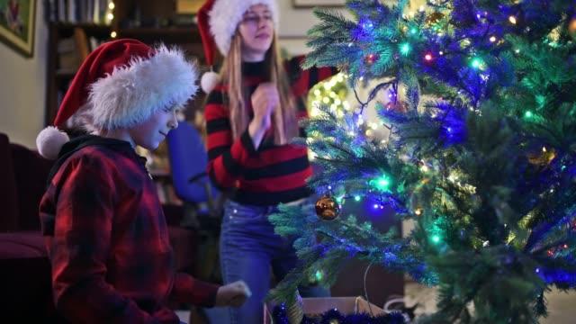 kids wearing santa hats decorating the christmas tree - imgorthand stock videos & royalty-free footage