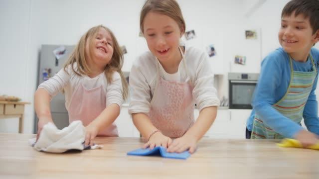 vídeos y material grabado en eventos de stock de los niños limpiando la mesa y divertirse - trapo de limpiar el polvo