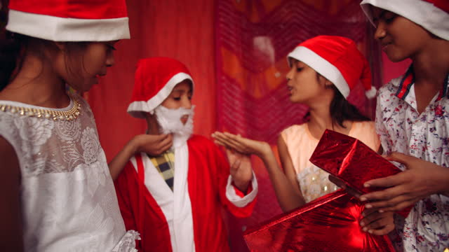 kids with santa hats bully playfully with the fake beard of their friend dressed as santa claus, also known as father christmas, saint nicholas, saint nick, kris kringle, or simply santa - weihnachtsmütze stock-videos und b-roll-filmmaterial