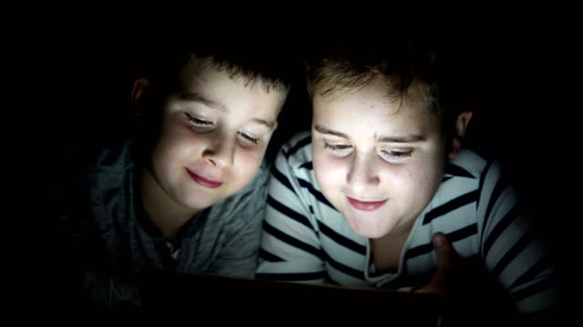 Kids with tablet computer in a dark room