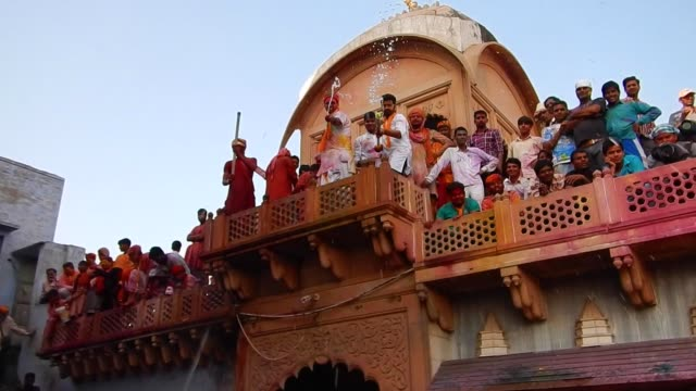 vídeos y material grabado en eventos de stock de kids with water pistol aim directly for the camera / religious festivities and celebrations inside the temple complex in nandgaon mathura the village... - krishna