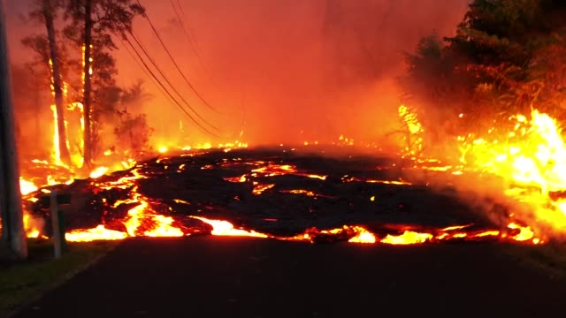 kilauea volcano lava flows down a street from a fissure during ongoing eruptions on hawaii's big island on may 27 2018 in pahoa hawaii - kilauea stock videos & royalty-free footage