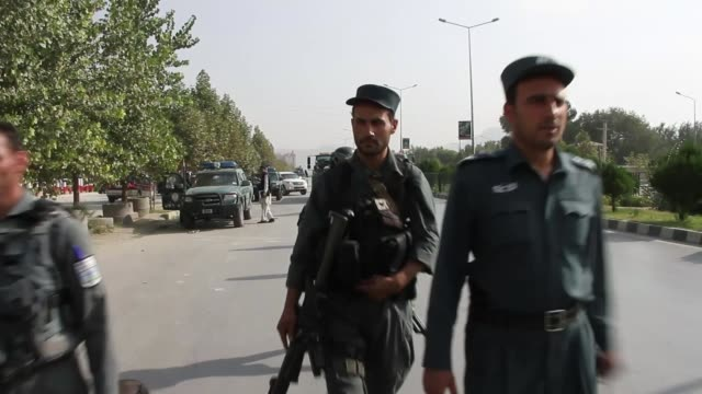 13 killed in attack on american university in kabul ext/day armed soldiers on guard on road leading to university security forces beside trucks... - kabul stock-videos und b-roll-filmmaterial