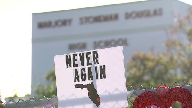 vidéos et rushes de 10 killed in texas school shooting t230218039 / florida parkland stoneman douglas high school ext sign 'never again' on fence pull focus school... - tirer