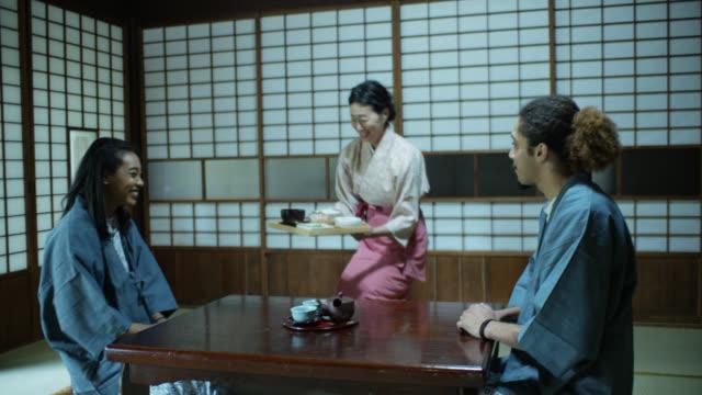 Kimono trägt Hostess bringt Essen für Gäste in Ryokan
