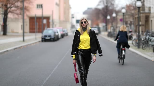 Kimyana Hachmann is seen wearing a red Chanel bag multi colored sneaker Chanel yellow Louis Vuitton hoody Valentino college jacket Ray Ban sunglasses...