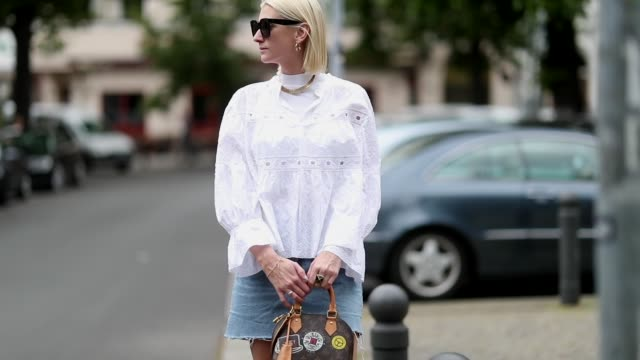 stockvideo's en b-roll-footage met kimyana hachmann is seen wearing white blouse chloe louis vuitton bag celine sunglasses vintage denim skirt white boots on may 18 2019 in berlin... - louis vuitton modelabel