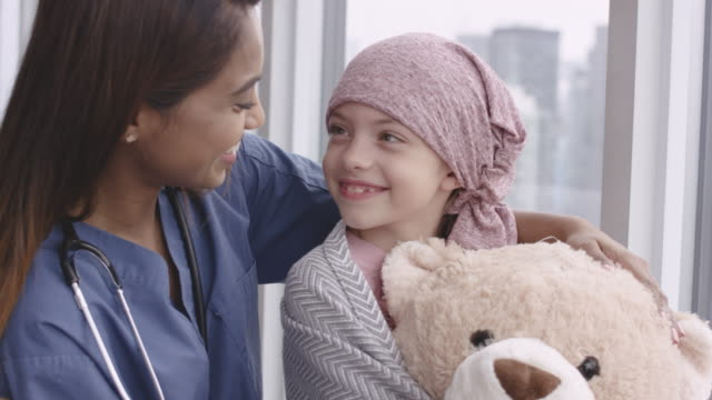 vídeos de stock e filmes b-roll de kind doctor comforts girl with cancer - cancro
