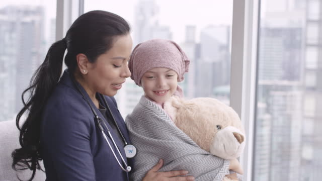 Kind doctor comforts girl with cancer