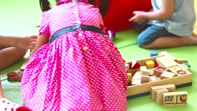 vídeos de stock e filmes b-roll de kindergarten, kids playing with blocks toy - cuidar de crianças