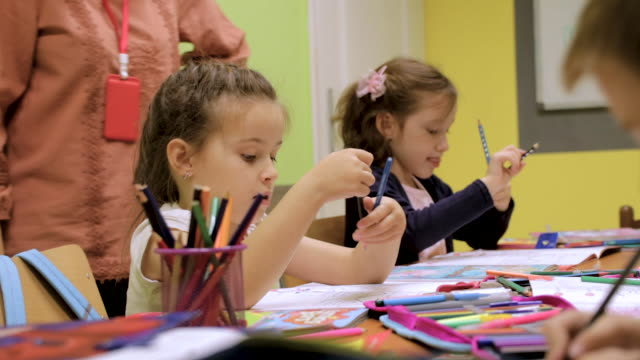 kindergarten students activities in classroom. preschool children coloring and writing together at their desk. teacher is standing next to them and giving them hints and encouragement. teacher with a group of preschool children in a nursery - child care stock videos & royalty-free footage