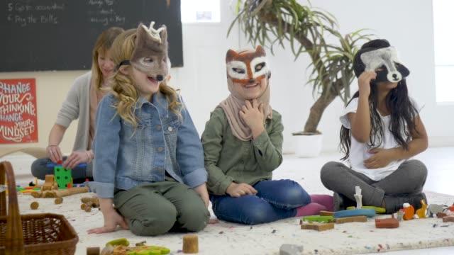 kindergarten schüler machen gruppenaktivität im klassenzimmer - kopfbedeckung stock-videos und b-roll-filmmaterial