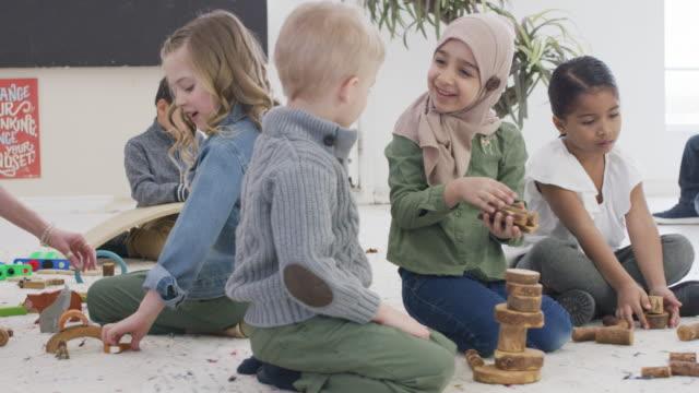 vídeos de stock e filmes b-roll de kindergarten students doing group activity in classroom - infantário