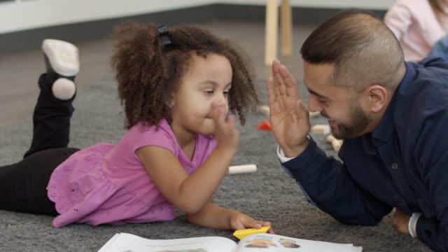 kindergarten teacher reading book to student - community centre stock videos & royalty-free footage