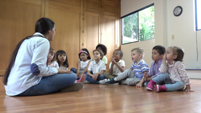 kindergarten teacher sitting on the floor with her class discussing a book - preschool stock videos and b-roll footage