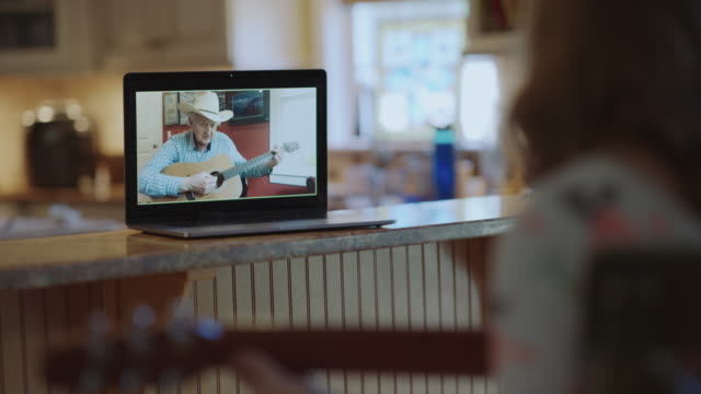 kindhearted grandfather teaches his granddaughter how to play the acoustic guitar via video call - over the shoulder stock videos & royalty-free footage