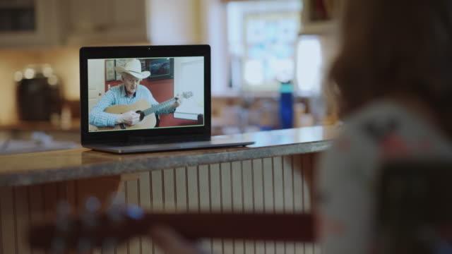 vídeos de stock e filmes b-roll de kindhearted grandfather teaches his granddaughter how to play the acoustic guitar via video call - sobre os ombros vista traseira