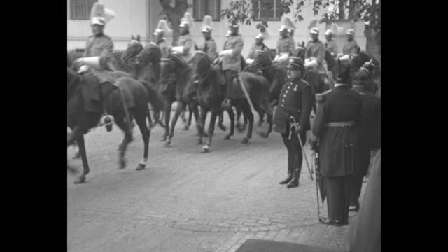 King accompanied by mother Princess Helena and surrounded by patriarchs attendants and soldiers gets into carriage carriage pulls away / Romanian...