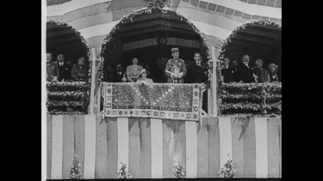 King Alexander I and Queen Maria in reviewing stand / schoolgirls march past waving greenery