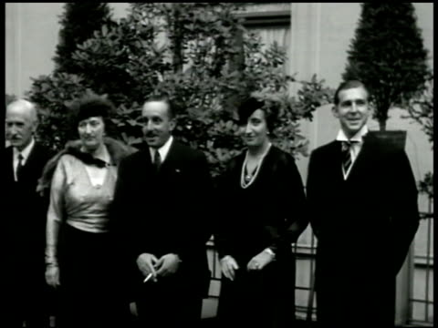 king alfonso xiii of spain standing outside smoking cigarette w/ wife princess victoria eugenie of battenberg next to him others unidentified. king... - documentary footage stock videos & royalty-free footage