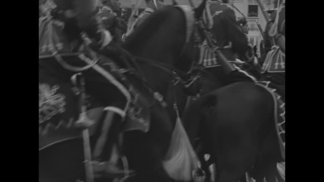 King Boris III salutes during troop review in Sofia Bulgaria / montage Bulgarian mounted soldiers ride past / horses pull carts with soldiers and...
