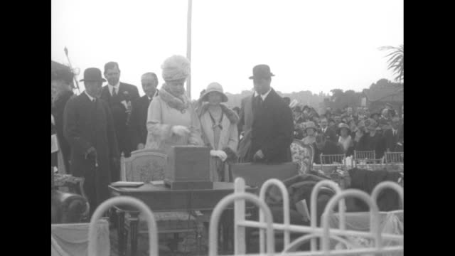 king george on reviewing stand doffs hat to others on stand queen mary climbing steps crowd in bg as the royal couple attends the royal air force... - acrobatica aerea video stock e b–roll