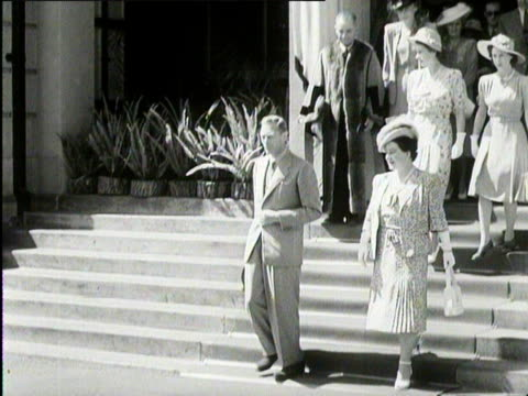 vídeos de stock, filmes e b-roll de king george vi and queen elizabeth walk down a stairway and get into their rollsroyce south africa 1947 - rolls royce
