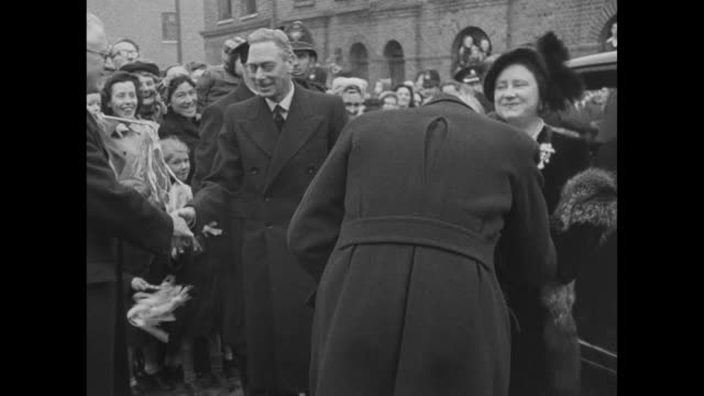 king george vi and wife queen elizabeth shake hands with officials after getting out of car / with officials they look at model of commercial... - イーストロンドン点の映像素材/bロール