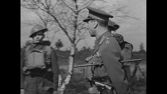 king george vi and wife queen elizabeth walk along path in field in front of line of canadian soldiers in combat gear / george and officer walk along... - gun stock videos & royalty-free footage