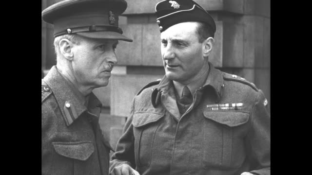 king george vi dressed in military uniform talks with captain charles brown commander of scottish guards / lieutenant general sir t ralph eastwood... - home guard britannica video stock e b–roll