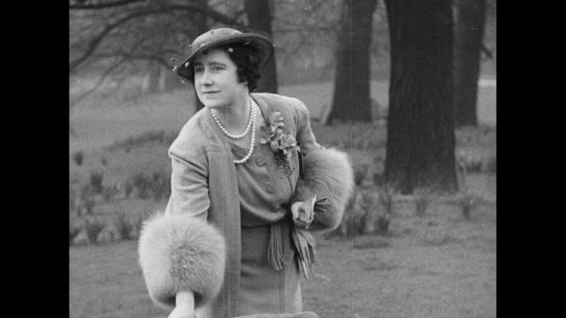 stockvideo's en b-roll-footage met ls king george vi queen elizabeth princess elizabeth and princess margaret stand near lake as corgi dogs frolic nearby / dogs and family stand on... - prinses margaret windsor gravin van snowdon