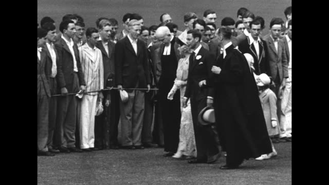 king george vi, queen elizabeth, princess elizabeth and princess margaret walk on the lawn at eton college / the king in top hat, the queen in long... - top hat stock videos & royalty-free footage