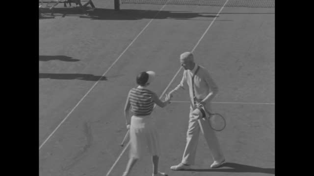 stockvideo's en b-roll-footage met king gustav v of sweden walks off tennis court in nice france / king shakes hands with female doubles partner as vo applause and they walk together... - koning koninklijk persoon