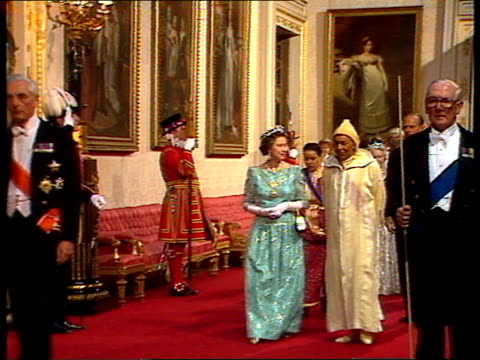 king hassan ii of morocco visits ; england: london: buckingham palace: int guests wearing evening dress towards on way to state banquet queen... - state dinner stock videos & royalty-free footage