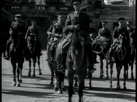King Leopold III in uniform on top of horse other mounted officers BG Belgium soldiers in full uniform marching down street King Leopold III on horse...