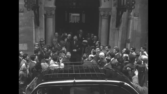 King Paul and Queen Frederica of Greece leaving Eglise Orthodoxe Grecque in Paris after service crowds surrounding church entrance and car camera...