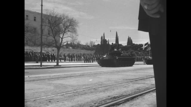 King Paul I of Greece salutes as youth file past at beginning of military parade / tanks in parade / truck tows artillery gun / three young women...