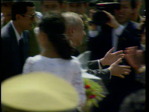 king sihanouk returning to cambodia after 13 years in exile walks smiling towards cambodian official kisses him on both cheeks phnom penh; 14 nov 91 - 追放点の映像素材/bロール