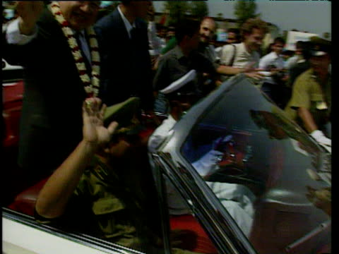 king sihanouk with garland of flowers round neck standing in open topped car waving at cameras celebrations of return to cambodia after 13 years in... - 追放点の映像素材/bロール