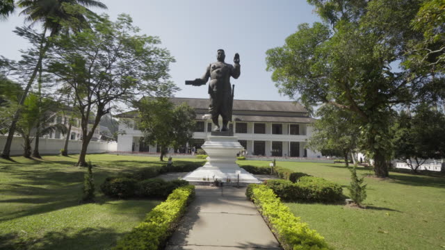 king sisavangvong statue by woman on footpath against famous theatre in city on sunny day - luang phabang, laos - off the beaten path stock videos & royalty-free footage